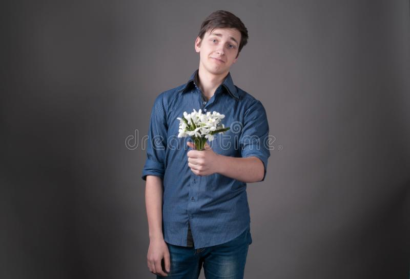 Confused young man in blue shirt holding in bouquet with snowdrops, looking at camera. And smiling on grey background royalty free stock photo