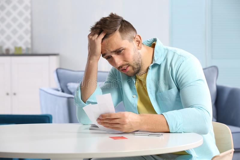 Confused young man calculating taxes royalty free stock photo