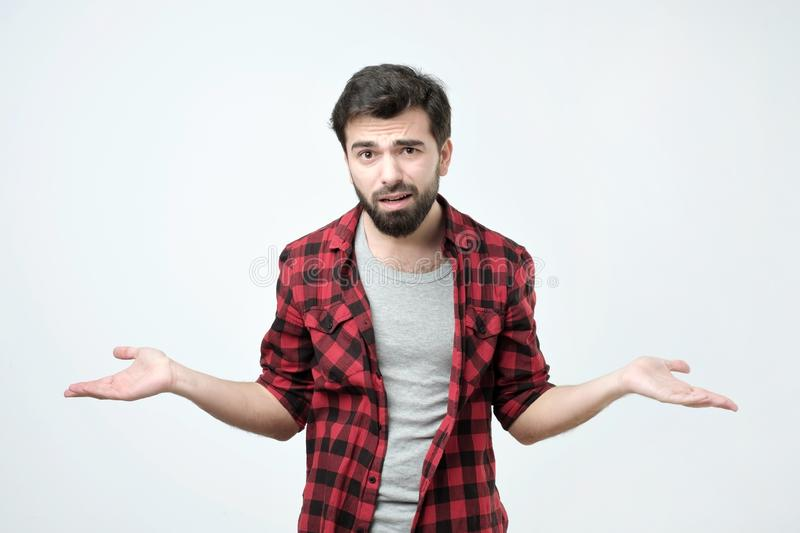 Confused young man dressed in black red shirt standing over white background. Gesturing with hands like he does not know what to choose royalty free stock images