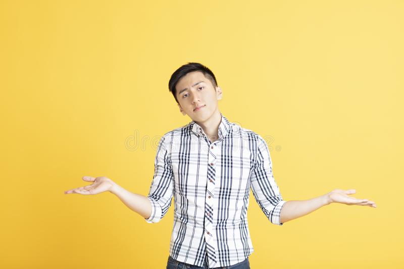 Confused young man shrugging shoulders. Confused young asian man shrugging shoulders royalty free stock images