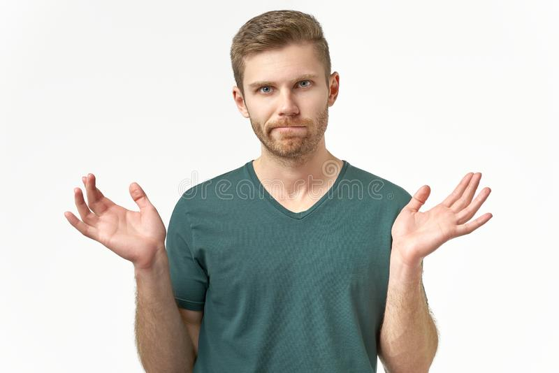 Confused young man spreads hands in different sides, feels uncertain, wears casual t shirt. Being puzzled by unexpected event stock image