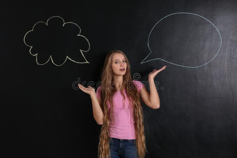 Confused young woman and blank speech bubbles on dark background royalty free stock image