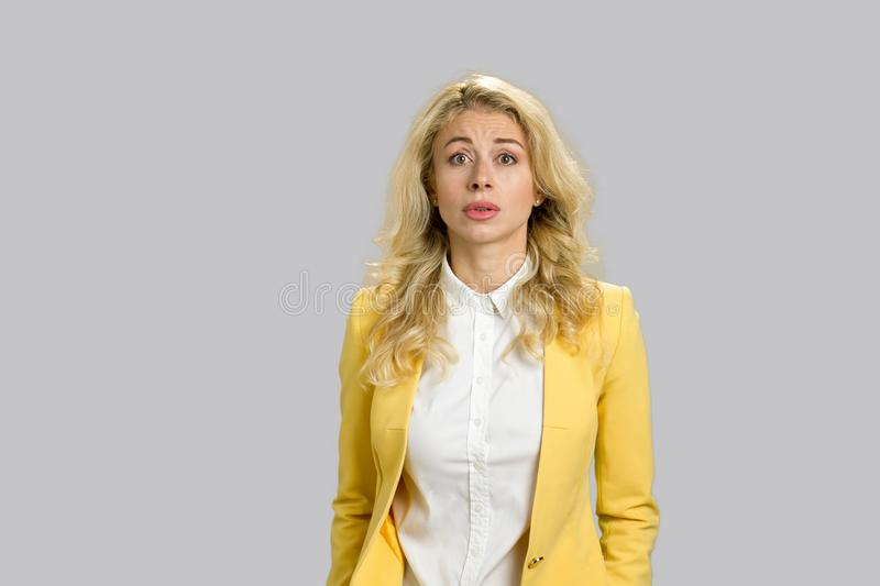 Confused young woman, grey background. stock photos