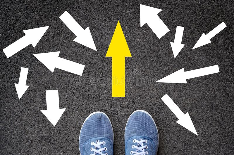 Confusing direction arrows on asphalt ground, feet and shoes on floor, personal orientation concept stock images