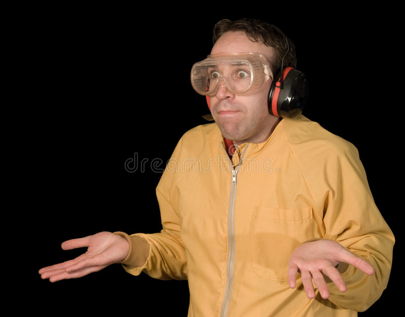Confusion On Black. A young industry worker looking utterly confused, isolated against a black background stock image