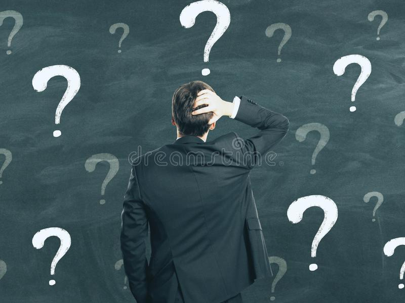Confusion and complexity concept. Back view of young businessman on chalkboard wall background with question marks. Confusion and complexity concept stock photography