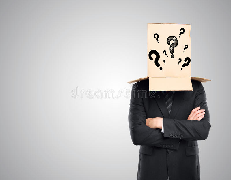 Confusion concept. Businessman with folded arms and cardboard box with question marks covering head on grey background. Confusion concept royalty free stock photography