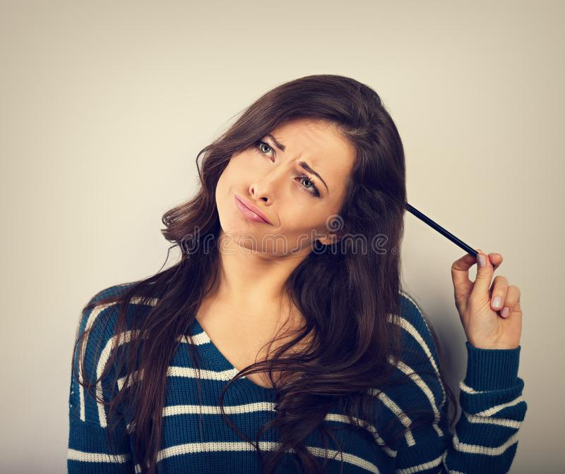 Confusion grimacing brunette woman thinking and looking up with question in eyes and pencil on the head in warm winter sweater. royalty free stock image