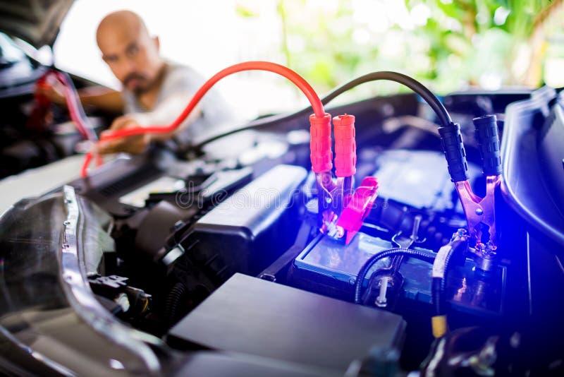 Confuso dell'accumulatore per di automobile cambiante del meccanico maschio, dell'accumulatore per di automobile della riparazion immagine stock libera da diritti