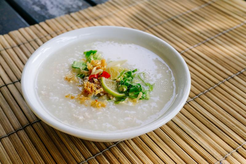 Congee del riso di stile o porridge tailandese del riso con i condimen dell'ingrediente fotografia stock