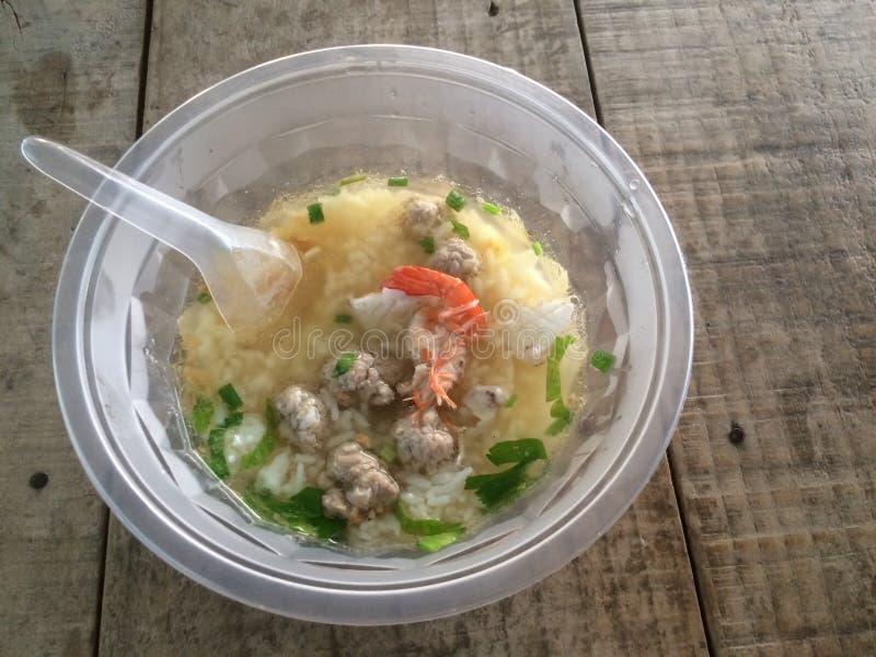 Congee do arroz misturado com o camarão, o calamar e a carne de porco na bacia e na colher plásticas imagem de stock