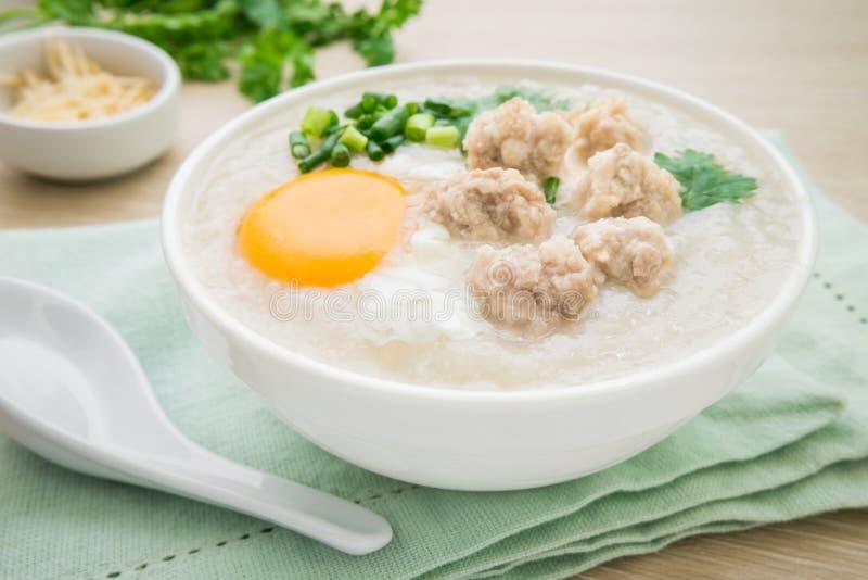 Congee met fijngehakt varkensvlees en gekookt ei in kom stock afbeelding