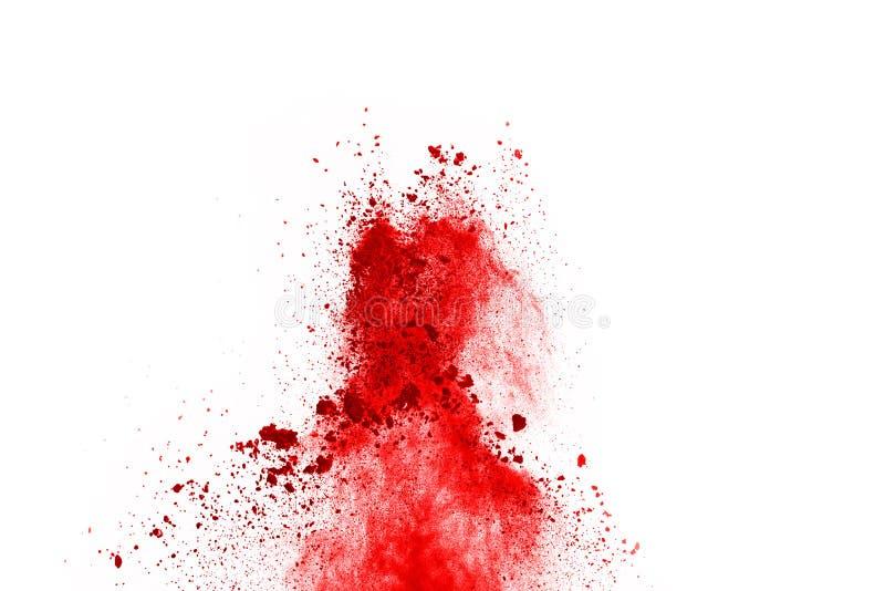 Congele el movimiento del polvo rojo que estalla, aislado en el fondo blanco foto de archivo libre de regalías