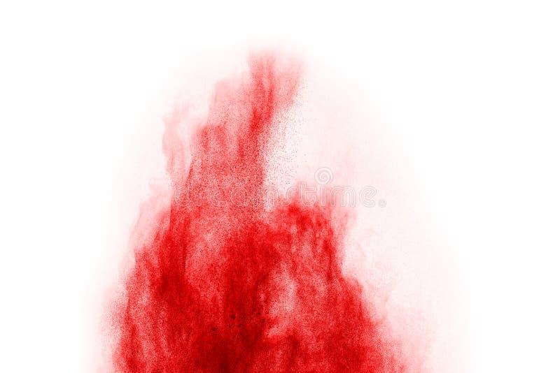 Congele el movimiento del polvo rojo que estalla, aislado en el fondo blanco fotos de archivo