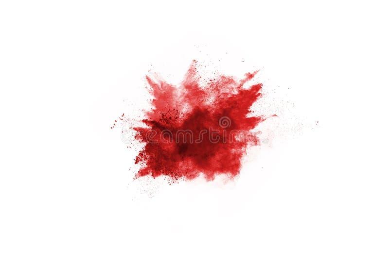 Congele el movimiento del polvo rojo que estalla, aislado en el fondo blanco fotografía de archivo