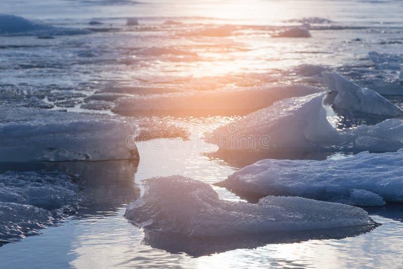 Congele rachado sobre a lagoa do inverno com fundo do tom do por do sol, Islândia imagens de stock royalty free