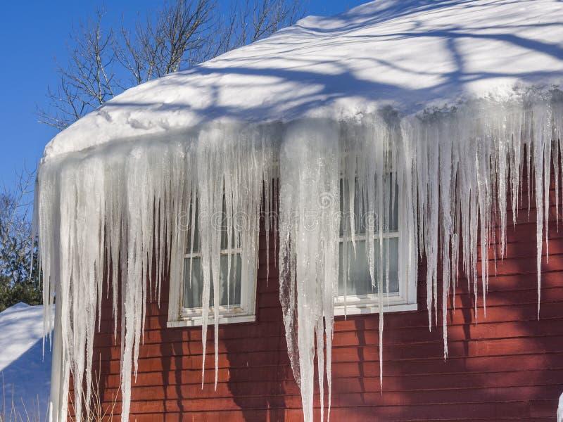 Congele represas e neve no telhado e nas calhas imagens de stock royalty free
