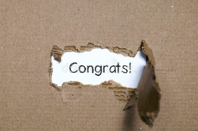 Congrats слова появляясь за сорванной бумагой стоковая фотография