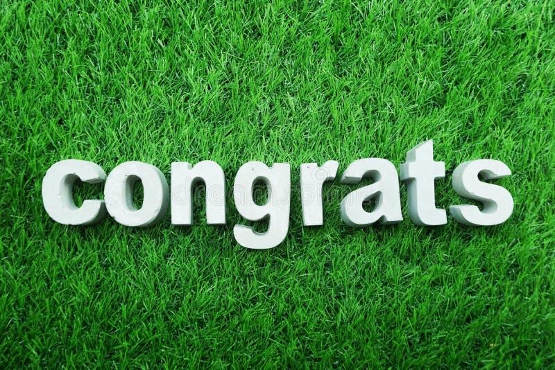 Congrats ha fatto dalla vista superiore dell'alfabeto concreto su erba verde fotografia stock