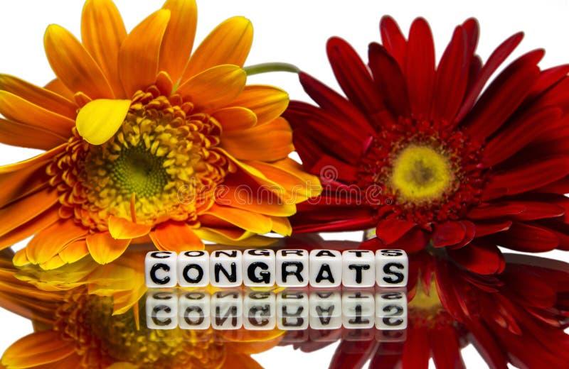 Congrats met rode en gele bloemen stock fotografie