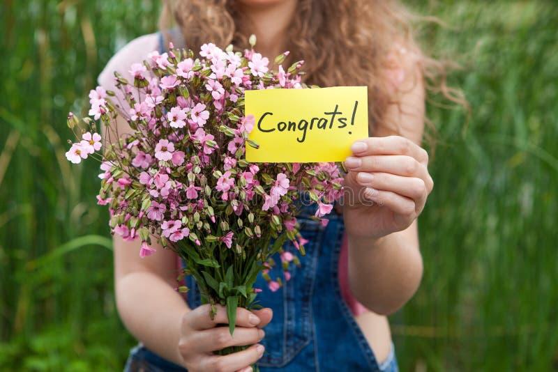Congrats - mulher bonita com cartão e ramalhete de flores cor-de-rosa fotografia de stock royalty free