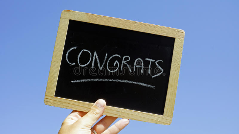 Congrats. Written on a chalkbord holding in the sun stock photography