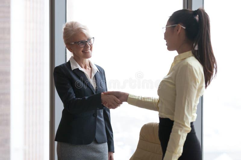 Congratula novo de sorriso do empregado do aperto de mão maduro da mulher de negócios imagem de stock