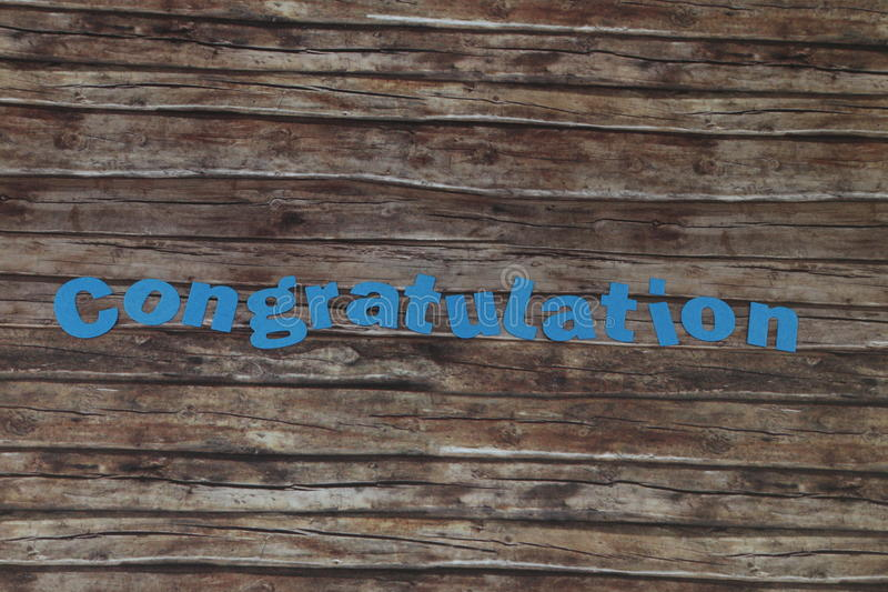 Congratulation. Blue title Congratulation on a brown background royalty free stock image