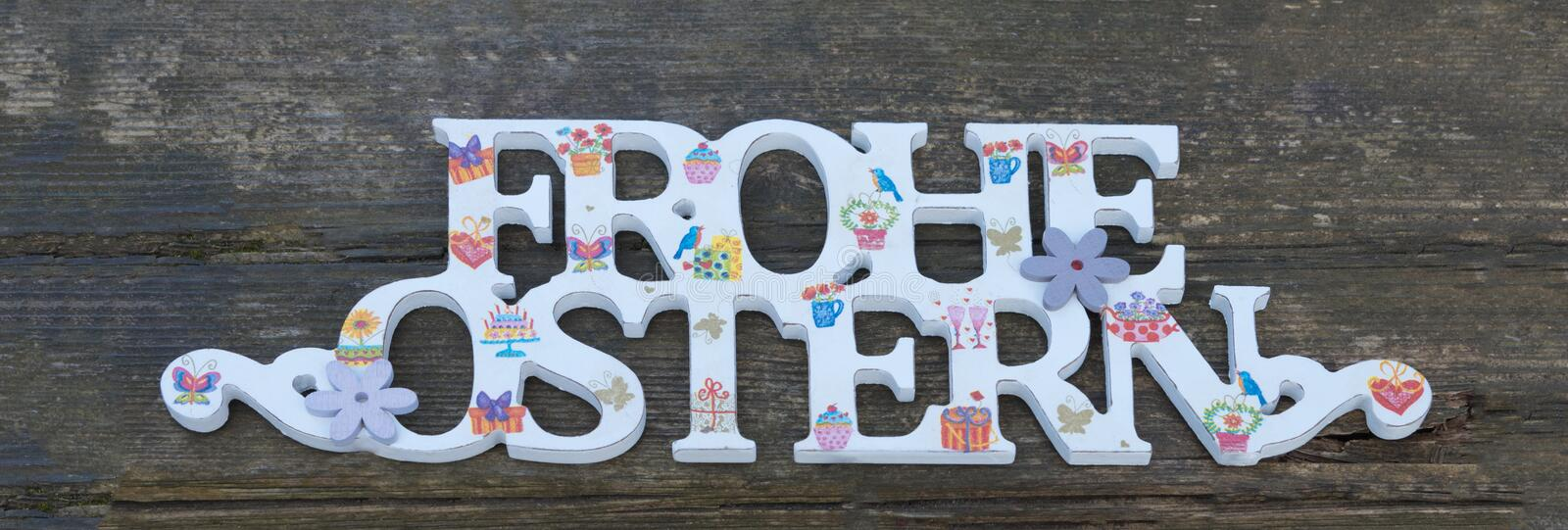 Congratulation Happy Easter in German. Decorated letters on wooden rustic background. Congratulation Happy Easter in German. Decorated letters, text on wooden stock images