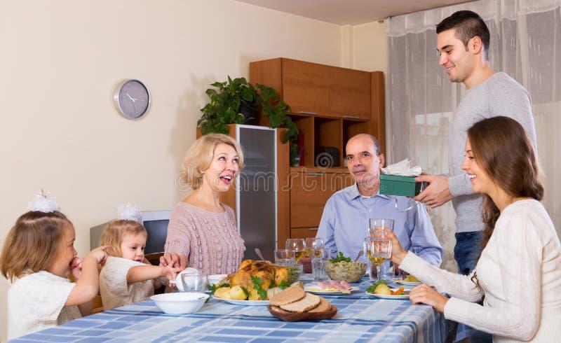 Congratulation heartily family at home. Young men congratulating heartily family member at home stock photos