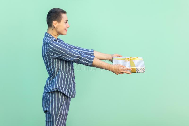 Congratulation! Side view portrait of beautiful with short hair young woman in striped suit standing, giving you present box, with stock photography