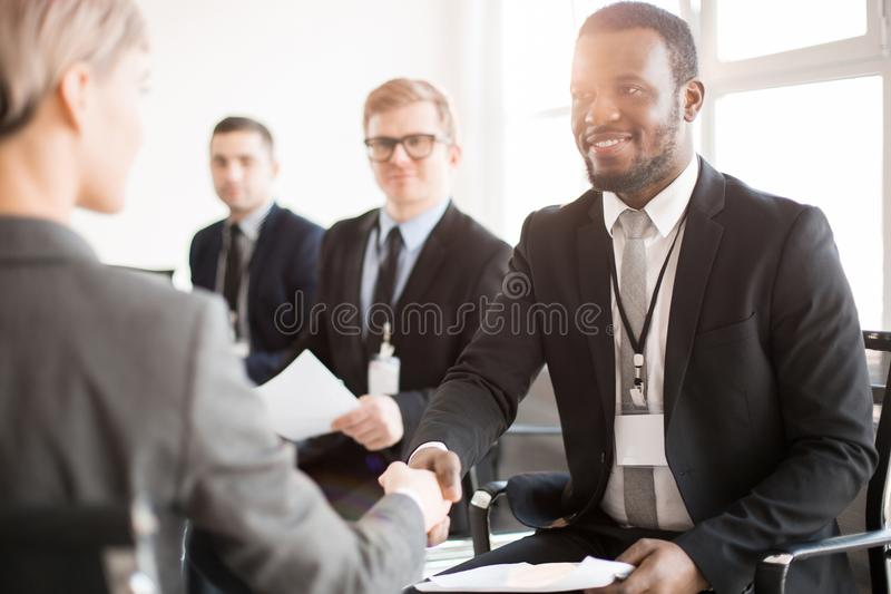 Congratulations. African-american broker in formalwear congratulating one of speakers on successful report at conference royalty free stock photo