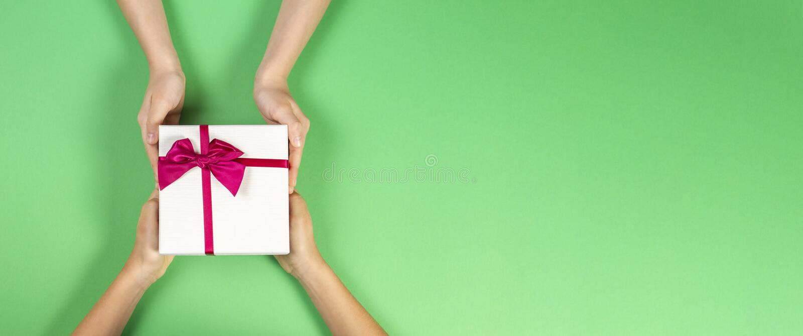Congratulations background. Top view of two persons hands giving and receiving a present gift box with ribbon on green. Background. Top view stock photos