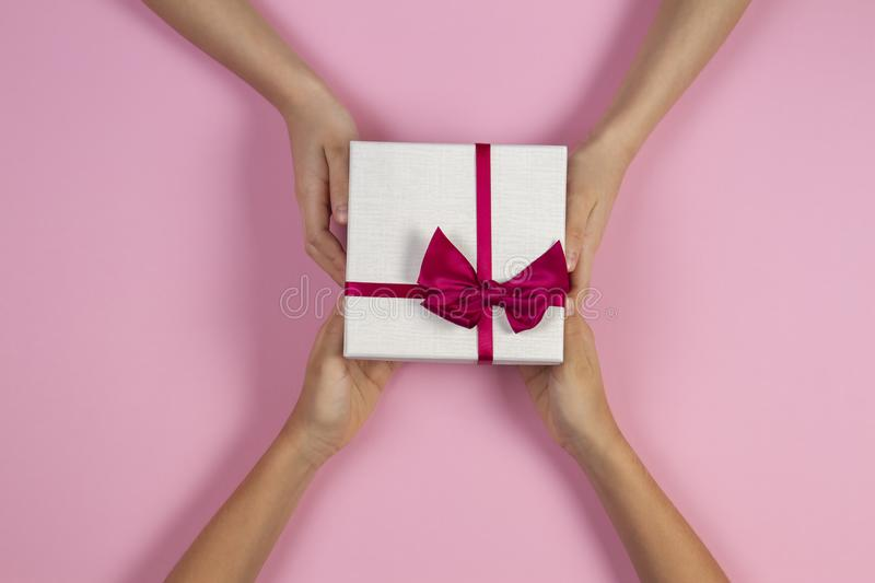Congratulations background. Top view of two persons hands giving and receiving a present gift box with ribbon on pink. Background. Top view stock photography