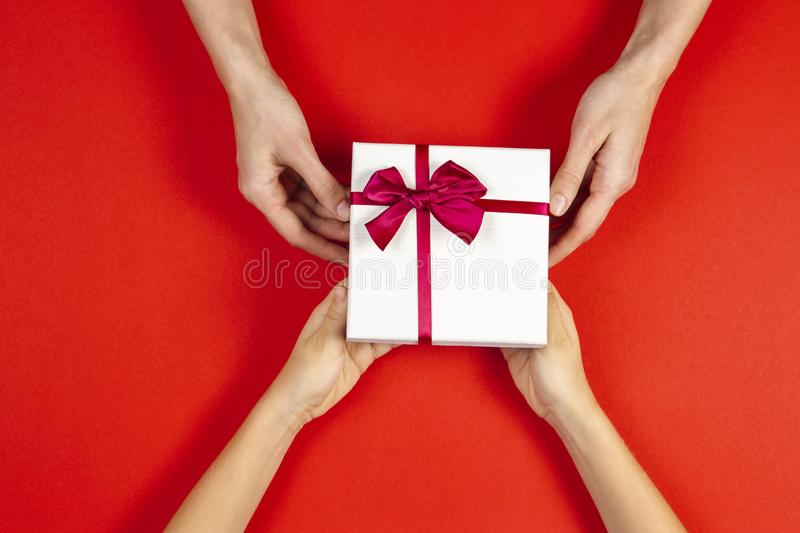 Congratulations background. Top view of two persons hands giving and receiving a present gift box with ribbon on red. Background. Top view royalty free stock photo