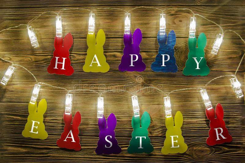 Congratulations on Easter. Color silhouettes of rabbits with written letters of white color royalty free stock images
