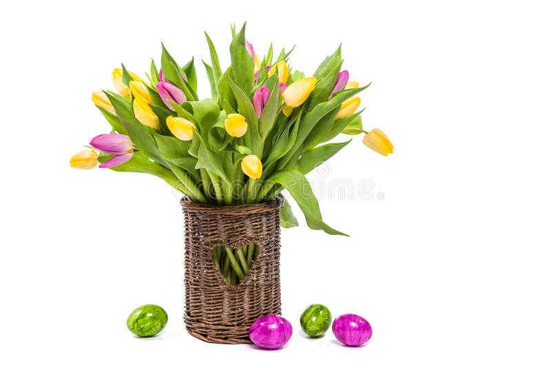 Congratulations on Easter. Tulips in a vase and easter eggs. Isolate on white background stock photography