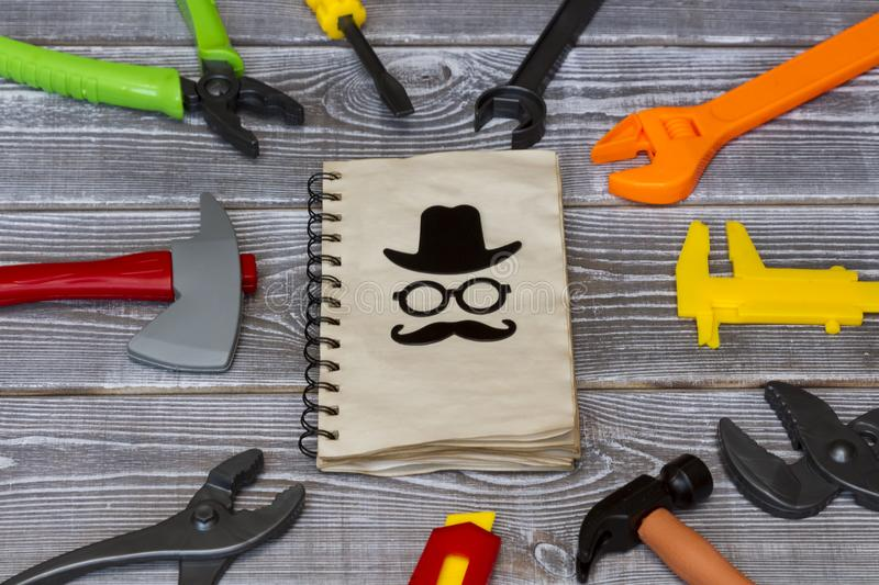 Congratulations Happy Fathers Day old notebook is surrounded by a toy tool on a rustic background. stock photos