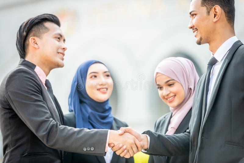 Congratulations! Muslim Asian business people shakes hand. Welcome onboard! Muslim Asian business people shaking hands with new partner, business co-working stock photos