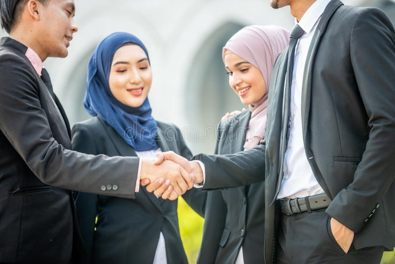 Congratulations! Muslim Asian business people shakes hand. Welcome onboard! Muslim Asian business people shaking hands with new partner, business co-working royalty free stock photo