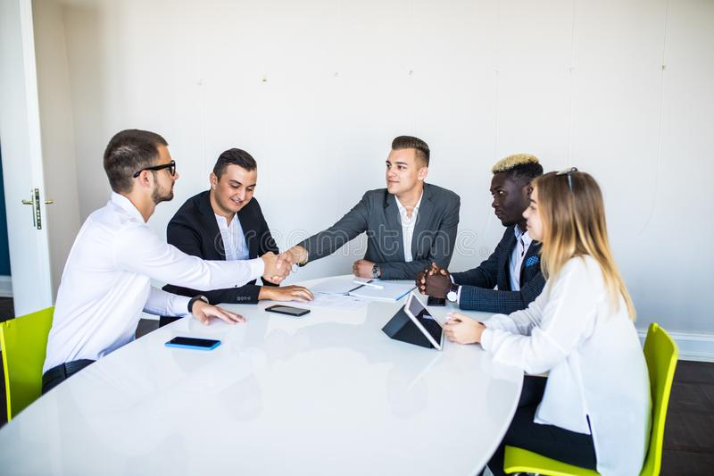 Congratulations. Two confident businessmen handshaking and smiling while sitting at the table together with their colleagues royalty free stock image