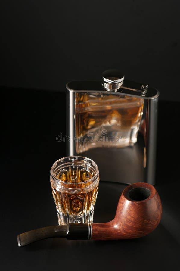 Conhaque, garrafa e tubulação fotografia de stock royalty free