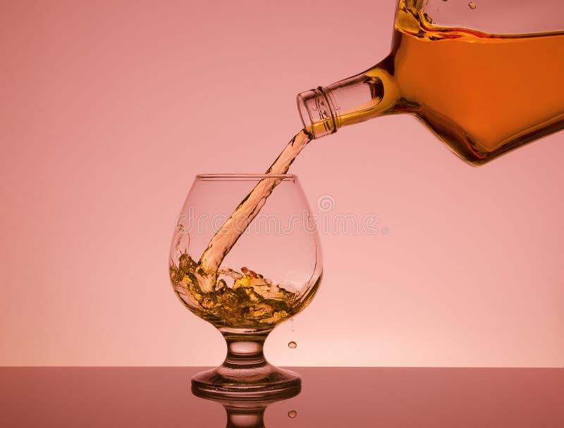 Conhaque que derrama da garrafa no vidro com respingo foto de stock