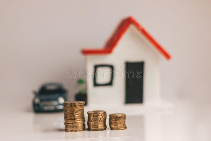Coni la pila con una casa vaga e l'automobile sui precedenti: bene immobile, proprietà, ipoteca, concetto finanziario di risparmi fotografia stock