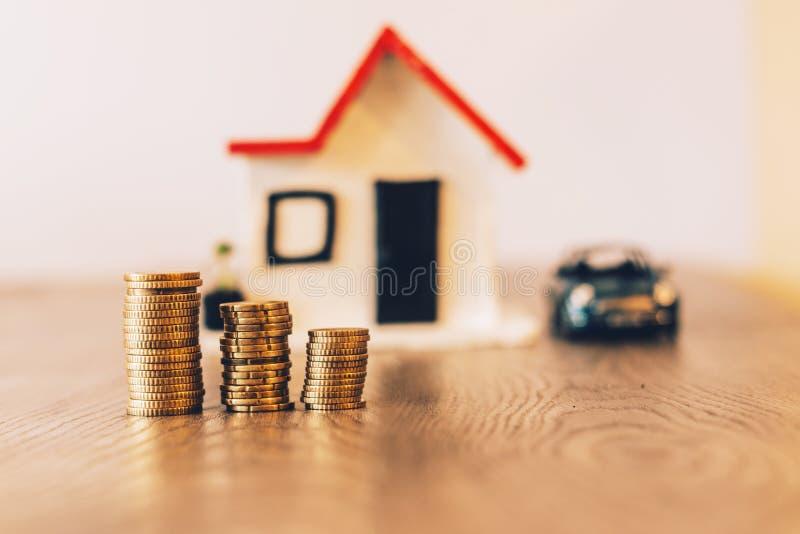 Coni la pila sopra una tavola di legno, con una casa e un'automobile vaghe sui precedenti: bene immobile, ipoteca della casa, con fotografia stock