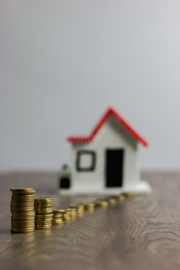 Coni la pila sopra una tavola di legno, con una casa vaga sui precedenti: bene immobile, ipoteca della casa, concetto di risparmi immagini stock libere da diritti