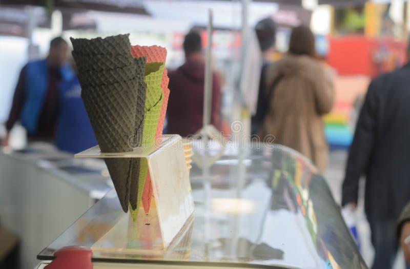 Coni vuoti Multicoloured per il gelato al venditore del gelato sulla via Scelta differente per l'amante del gelato immagini stock