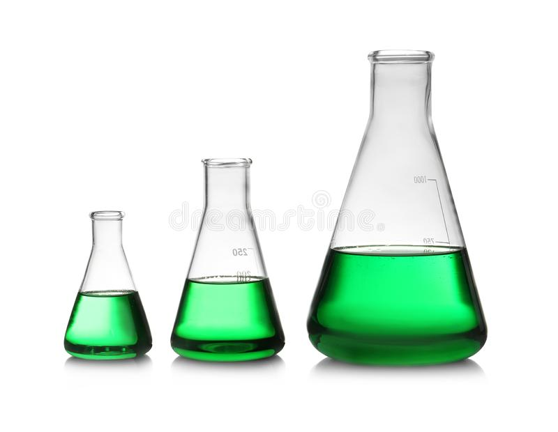 Conical flasks with green liquid on background royalty free stock photography