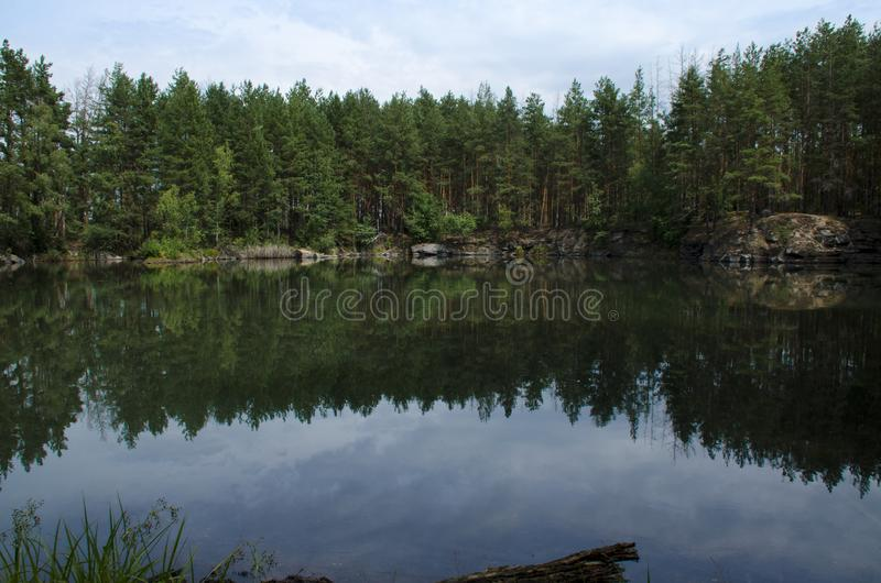 Coniferous forest is reflected in a lake with granite shores stock photos