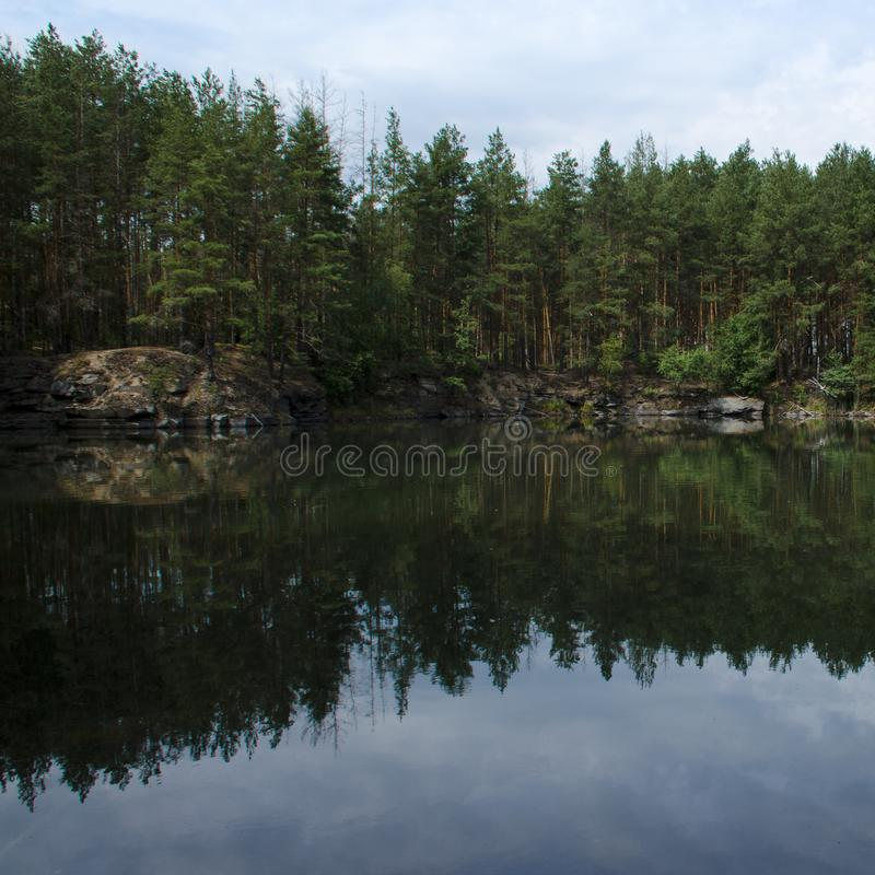Coniferous forest is reflected in a lake with granite shores stock photo